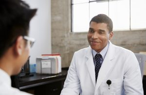 Prophet Climate Ministries smiling-mixed-race-male-doctor-in-consultation-76JH3G4-300x195 Smiling mixed race male doctor in consultation with patient